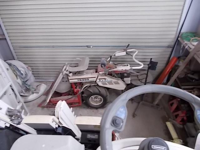 乾燥機の横に小型の稲刈り機がある